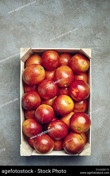 Blood oranges in a wooden box on a grey textured background