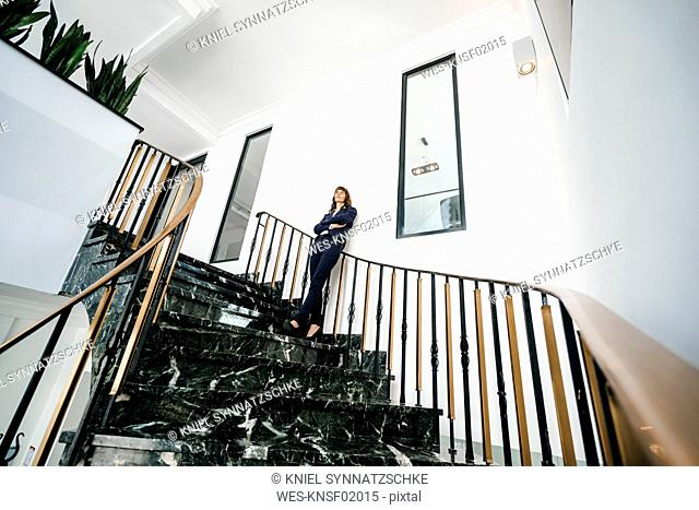Successful businesswoman standing on staircase