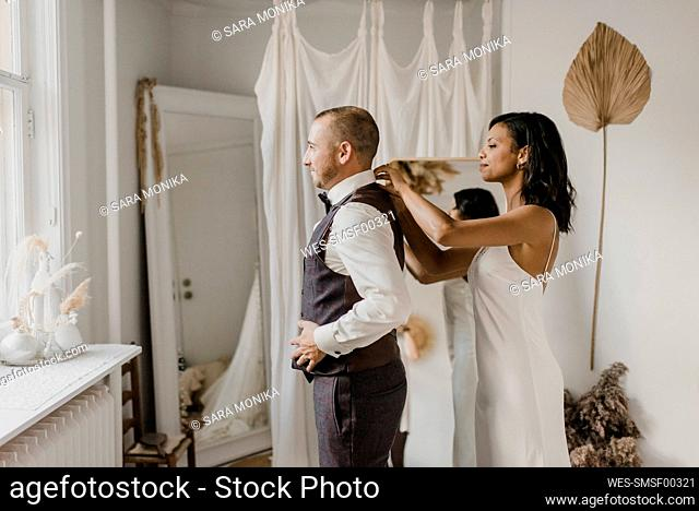 Young bride tying bow to bridegroom while standing at home