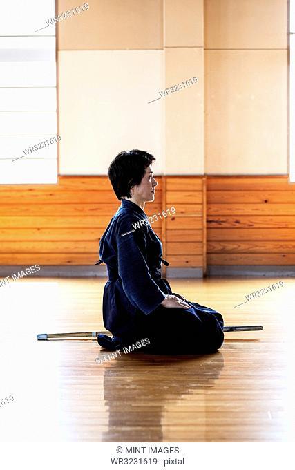 Side view of female Japanese Kendo fighter kneeling on wooden floor