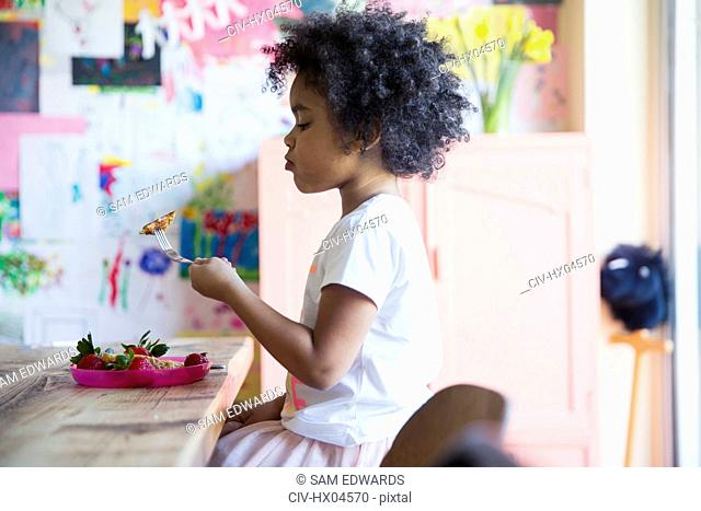 Curious girl eating breakfast at table