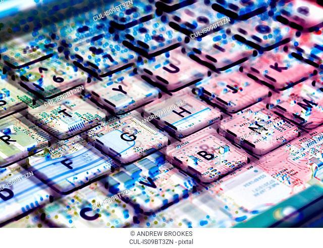 Multiple exposure of laptop computer showing keyboard and circuit board below