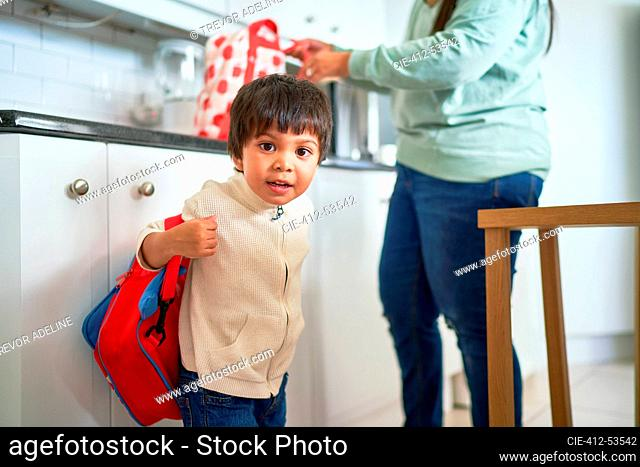 Portrait cute boy with backpack in kitchen
