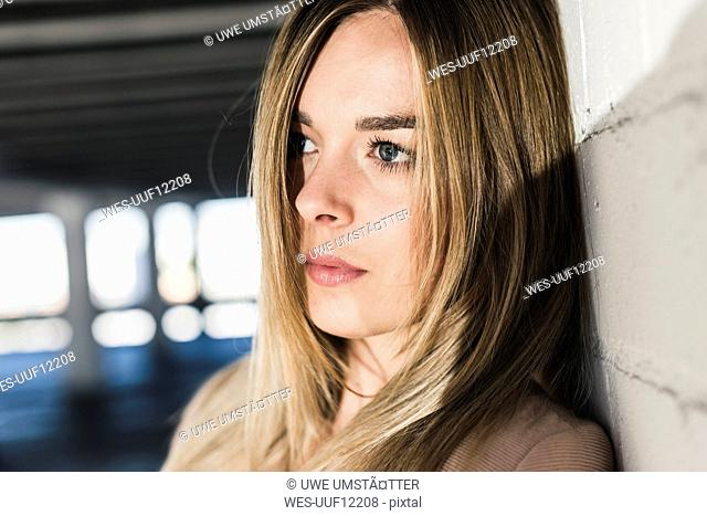 Thoughtful young woman leaning against a wall