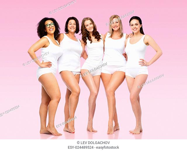 friendship, beauty, body positive and people concept - group of happy women different in white underwear over pink background
