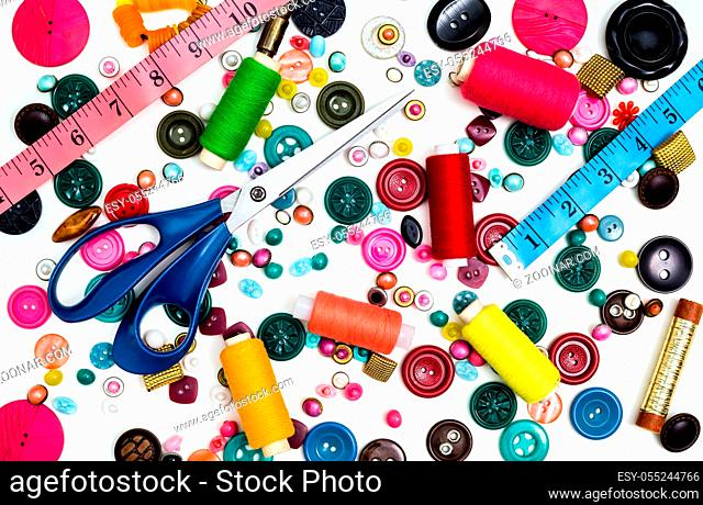 Sewing accessories for handmade sewing on a white background a spool of thread, scissors, buttons. Set for needlework. View from above
