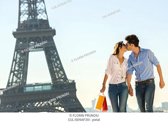 Young couple kissing near Eiffel Tower, Paris, France