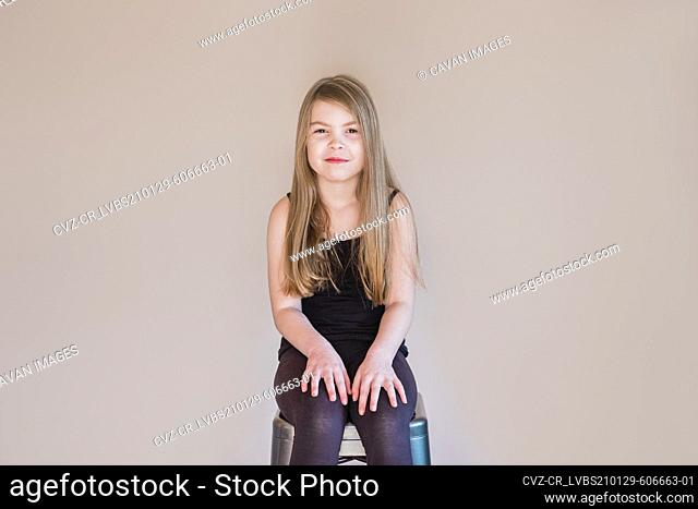 Young happy girl sitting on a stool inside