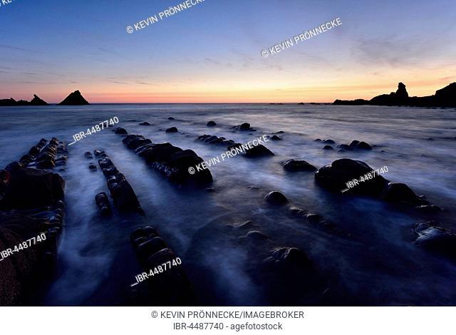 Rocks in the sea, rocky coast in the evening light, Atlantic Coast, Hartland Quay, Devon, United Kingdom