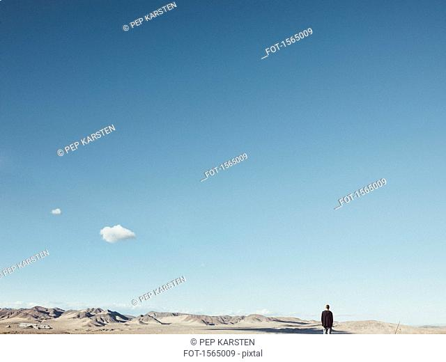 Rear view of man standing on barren landscape against blue sky, San Bernardino, California, USA