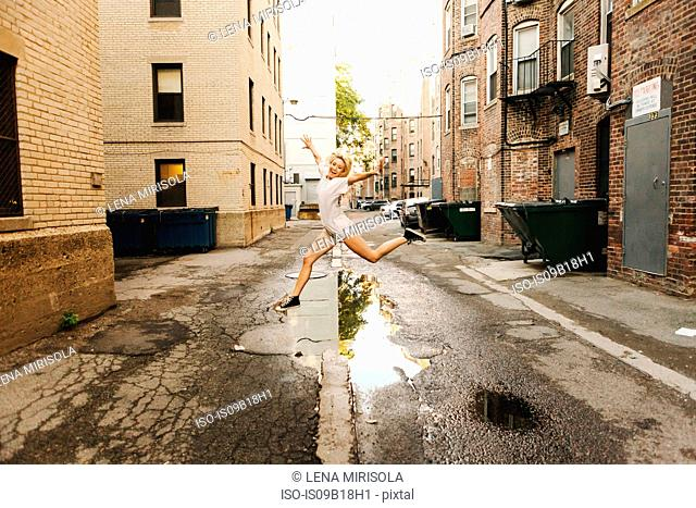 Woman jumping over puddle on road, Boston, MA, USA