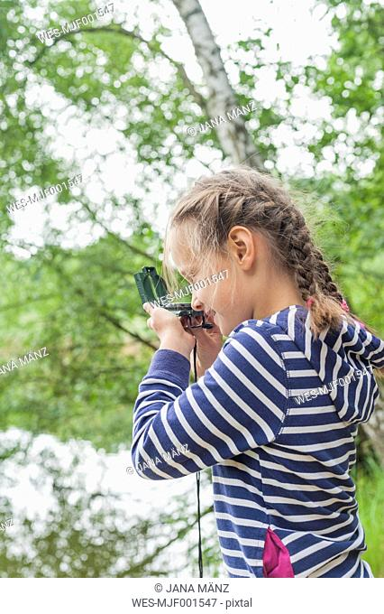 Germany, Girl looking through compass