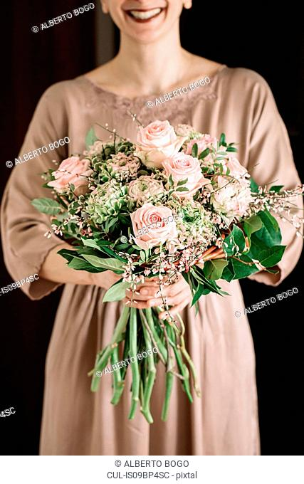 Woman holding bouquet of fresh soft pink roses