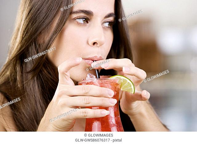 Close-up of a young woman drinking a cocktail
