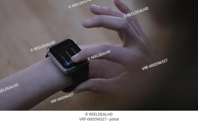 Young adult woman using smart watch at home on kitchen table