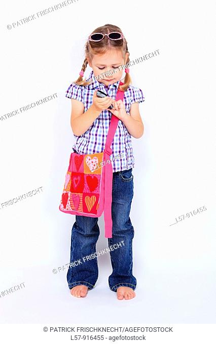 little girl standing with mobile phone and handbag over shoulder wearing sunglases, Switzerland