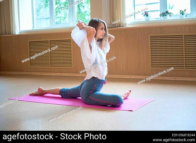 Young acrobatic woman with blonde hair sitting on the yoga mat and doing stretching exercises. Mid shot