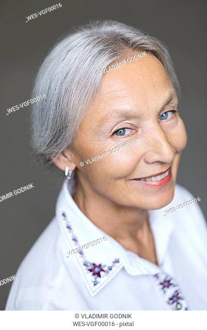 Portrait of smiling enior woman with grey hair and blue eyes