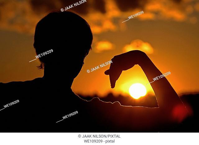 Woman silhouette holding arm around sun