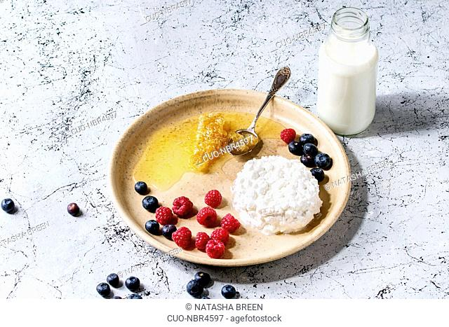 Ceramic plate of homemade cottage cheese served with blueberries, raspberries, bottle of milk and honeycombs over white marble texture table as background