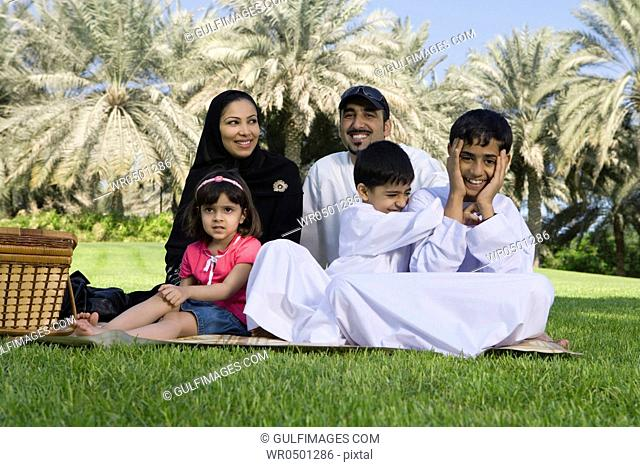 Family sitting together at park, smiling