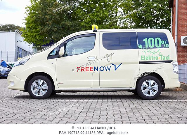 """12 July 2019, Hamburg: A Nissan e-NV 200 Evalia with the inscription: """"""""100% electric taxi"""""""" stands on a parking lot. The taxi entrepreneur Konstantin..."""