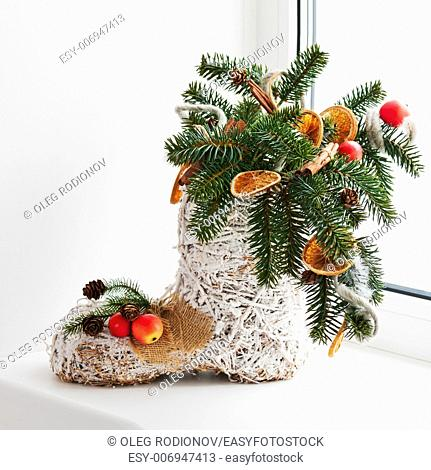 Christmas arrangement of felt boot decorated with toys. Closeup