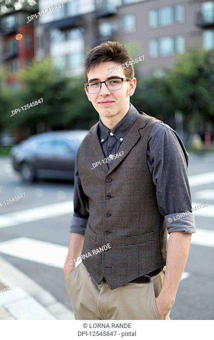 Portrait of a young man wearing formal clothing and standing along an urban street; Bothell, Washington, United States of America