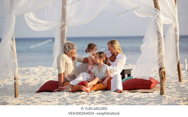 Mature parents enjoying some family bonding time on a beach with their young daughters