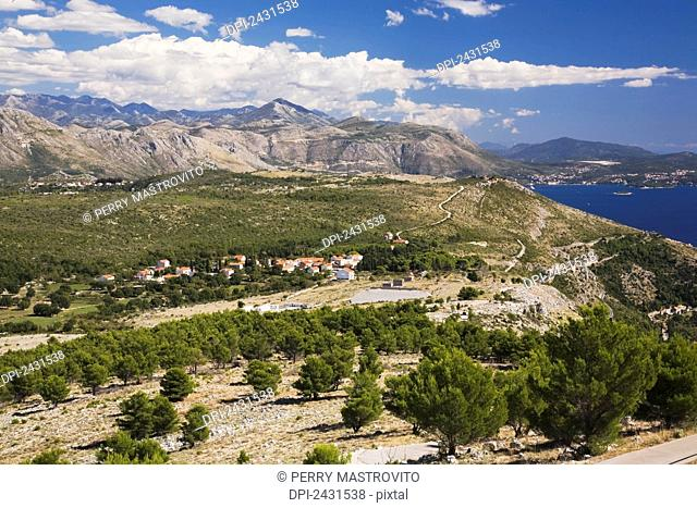 Aleppo pine tree (Pinus halepensis) forest and mountain landscape with small village taken from Mount Srd; Dubrovnik, Dalmatia region, Croatia