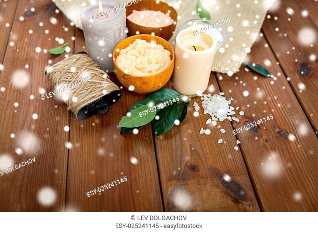 beauty, spa, therapy, natural cosmetics and wellness concept - body scrub with himalayan pink salt and candles on wood over snow