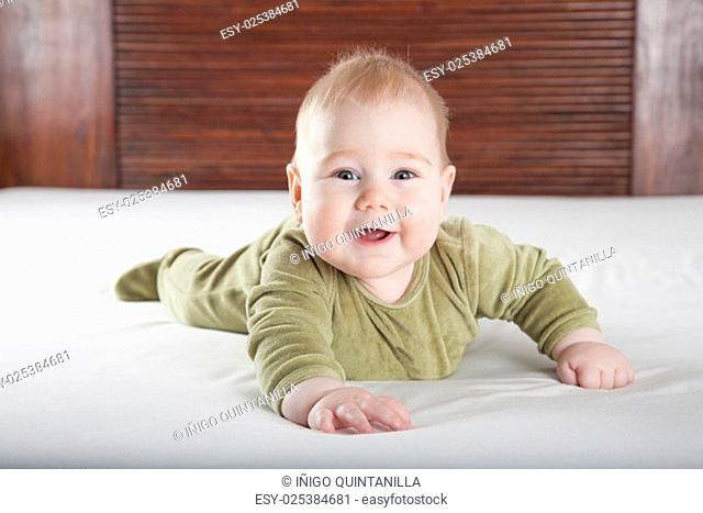 six months age blonde baby green velvet onesie lying on white sheet bed with brown wood background smiling happy face