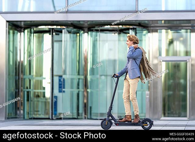Young businessman riding electric push scooter on footpath