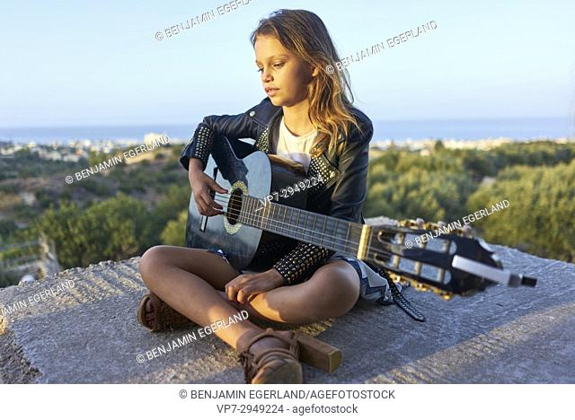 sensual young girl playing guitar passionated outside in nature. Australian ethnicity. During holiday stay in Hersonissos, Crete, Greece