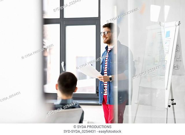 creative man with papers at office presentation