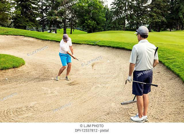 Two male golfers standing in a bunker, one holding a rake and waiting his turn, while the other swings at the ball to chip it out of the sand pit; Edmonton