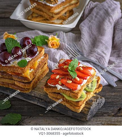 French toast from white bread with cottage cheese, strawberries, kiwi, cherries on a gray wooden board, top view