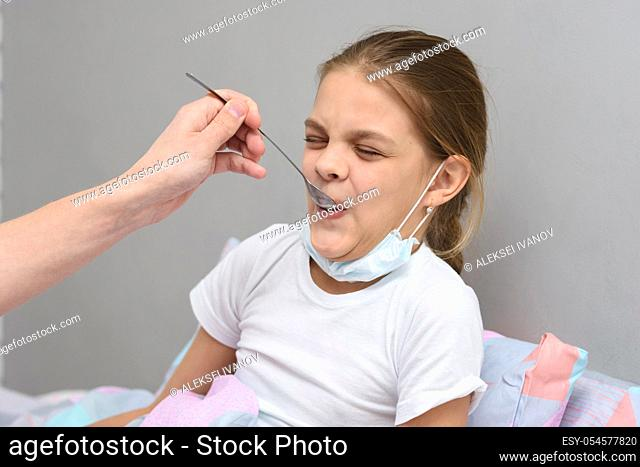 Girl drinking a very nasty medicine from a spoon