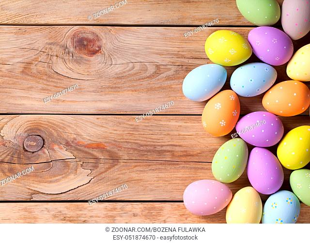 Easter background with Easter eggs on wooden table. Top view. Copy space