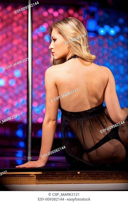 Back view of sexy blond striptease dancer. Sitting on stage in black see through dress