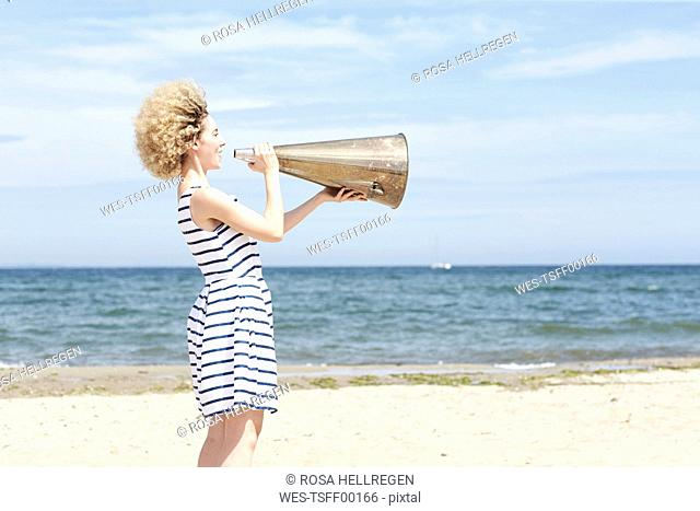 Young woman with megaphone on the beach