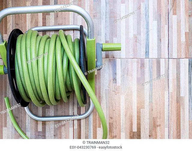 Green rubber hose of the plastic reel set on the wooden pattern tile for use in the home garden