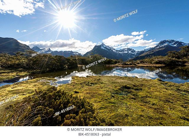 Sun shining on small mountain lake with reflection of a mountain chain, Key Summit Track, Fiordland National Park, Southland Region, New Zealand