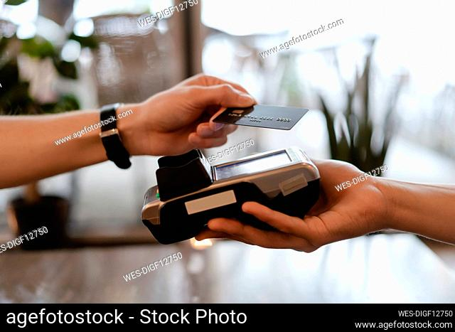 Man with protective mask paying with credit card in restaurant