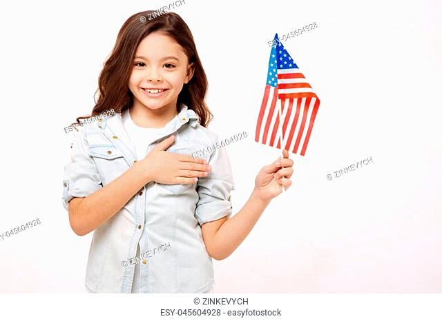 Proud for my nation. Cheerful smiling happy girl holding the American flag and touching her chest while expressing happiness and standing against white...