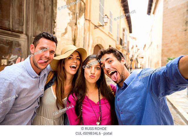 Couples making faces and taking selfie on street, Palma de Mallorca, Spain
