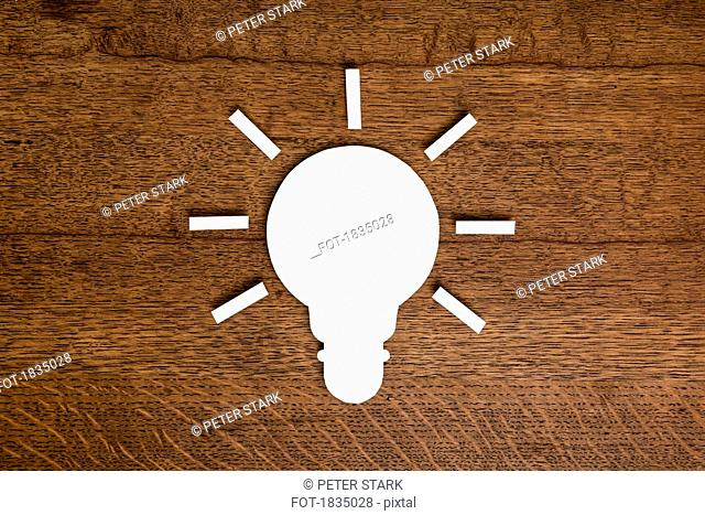 View from above paper light bulb on wooden surface