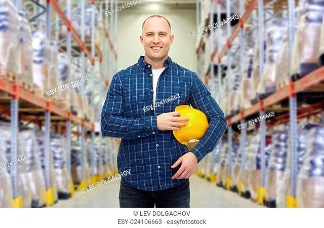 storage, shipment, logistic business, people and export concept - happy man with hardhat over warehouse background