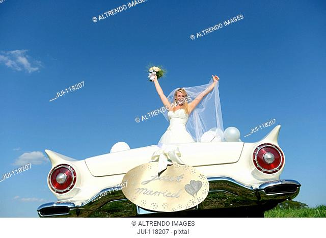 Bride With Bouquet In Open Top Car On Wedding Day
