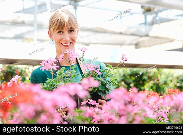 Gardener woman in her greenhouse with flowers for sale looking into the camera